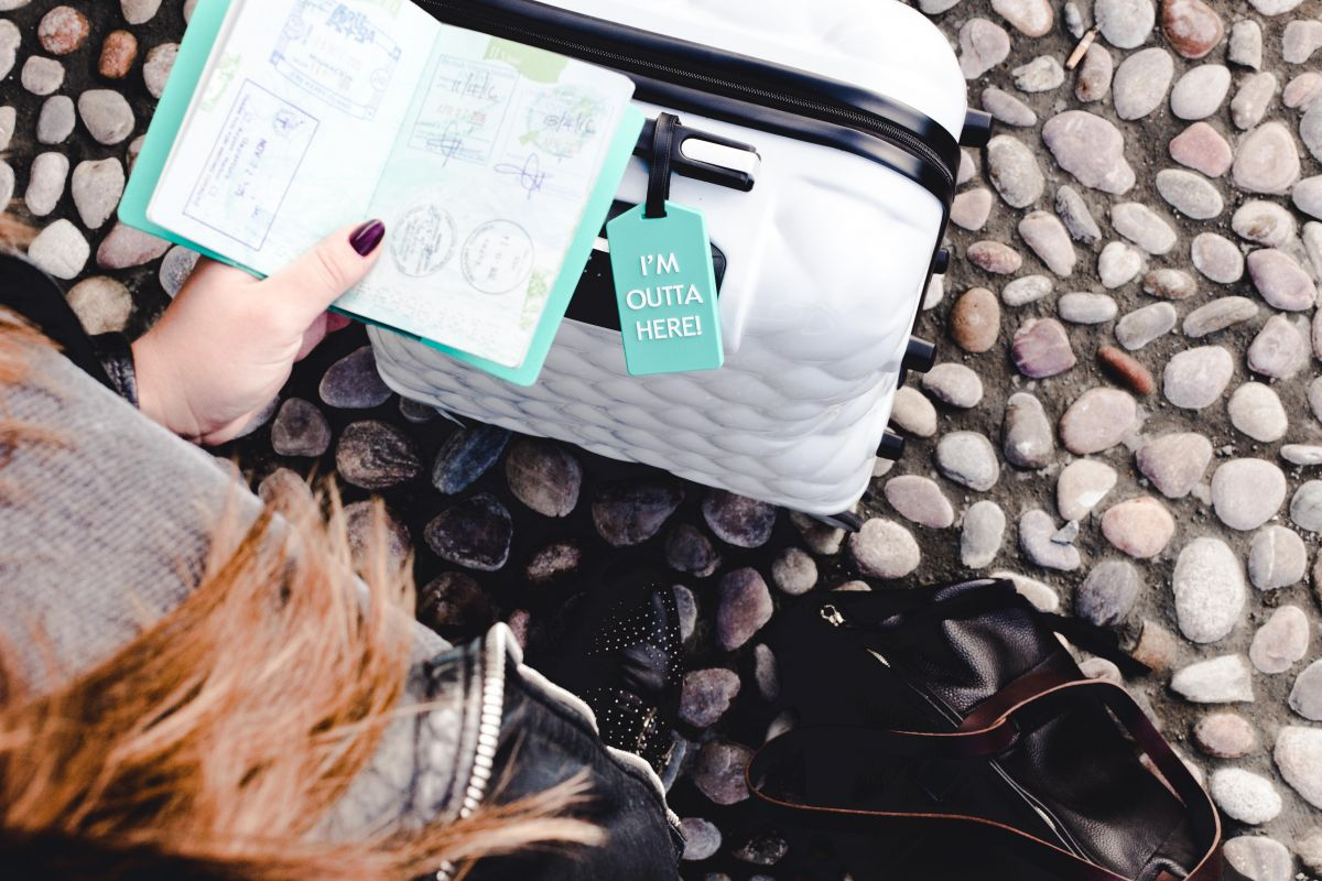 Photo of passport and suitcase with 'I'm outta here' luggage tag